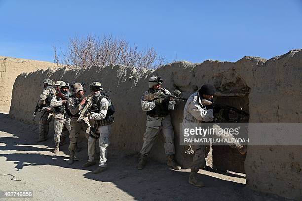 Afghan police forces check a dwelling during an antiTaliban operation in the Andar district of Ghazni province on February 4 2015 Afghan police...