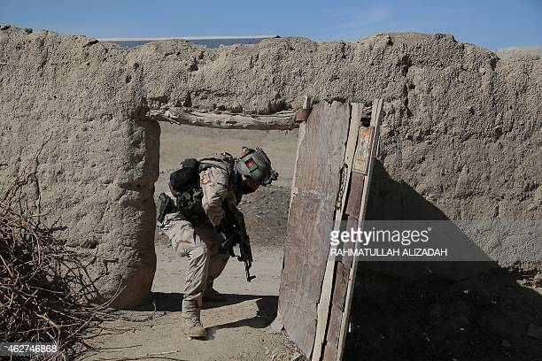 Afghan police forces enter a courtyard during an antiTaliban operation in the Andar district of Ghazni province on February 4 2015 Afghan police...