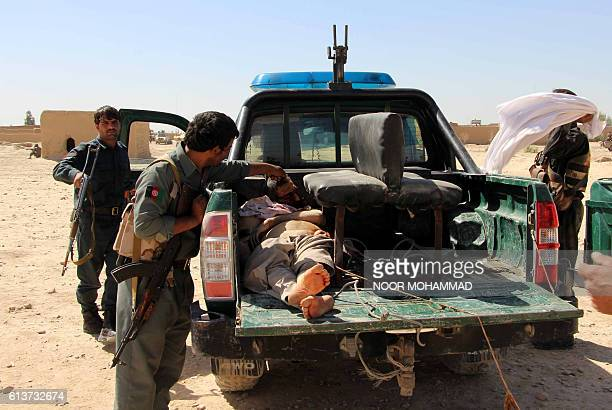 TOPSHOT Afghan police men looks on at a body of a Taliban militant during an ongoing battle between Taliban militants and Afghan security forces in...