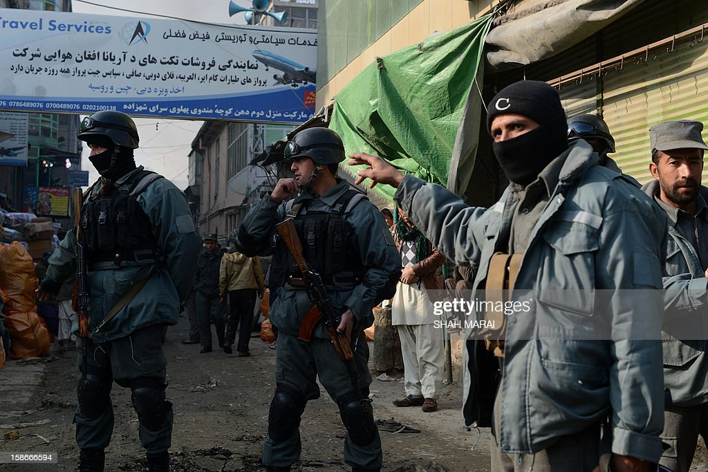 Afghan police personnel cordon off a street after a huge fire swept through a market in Kabul on December 23, 2012. A huge fire swept through a market in downtown Kabul on December 23, destroying hundreds of shops and forcing the city's nearby money exchange to evacuate, police and witnesses said. There were no reports of any casualties in the early morning blaze which destroyed most of the cloth market's 500 shops, Kabul fire department officials told AFP. AFP PHOTO/ SHAH Marai