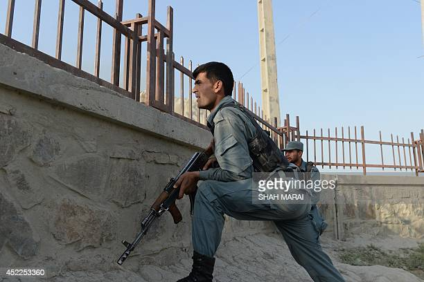 Afghan police take cover near the site of a suicide attack in front of Kabul's military airport on July 17 2014 Explosions and gunfire rang out after...