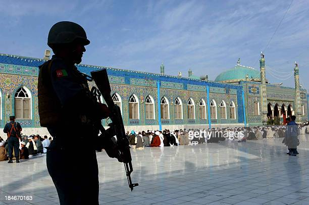 Afghan policeman keep watch as worshippers offer EidalAdha prayers in the main mosque in the city of MazariSharif in Balkh province on October 15...