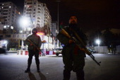 Afghan policemen block a road as they stands guard near the security perimeter setup around the Serena hotel in Kabul early on March 21 2014 Security...