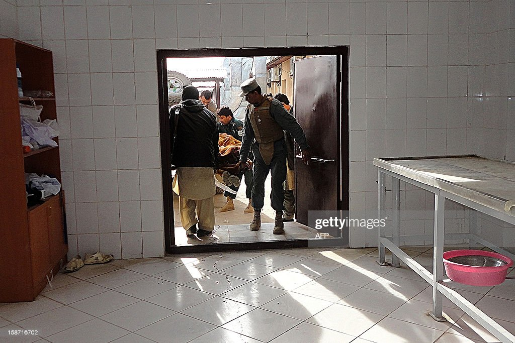 Afghan policemen carry the dead body of a civilian into a hospital morgue following a suicide attack in Khost province on December 26, 2012. A Taliban suicide car bombing hit a US-run base in eastern Afghanistan on December 26, killing at least three Afghans and wounding seven others, officials said. AFP PHOTO/ Mohammad Rasool Adil
