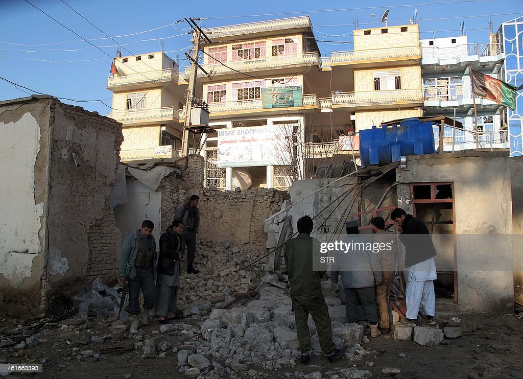 Afghan policemen check the site of a suicide attack in Lashkar Gah in Helmand province on January 10 2014 Three suicide attackers killed one...