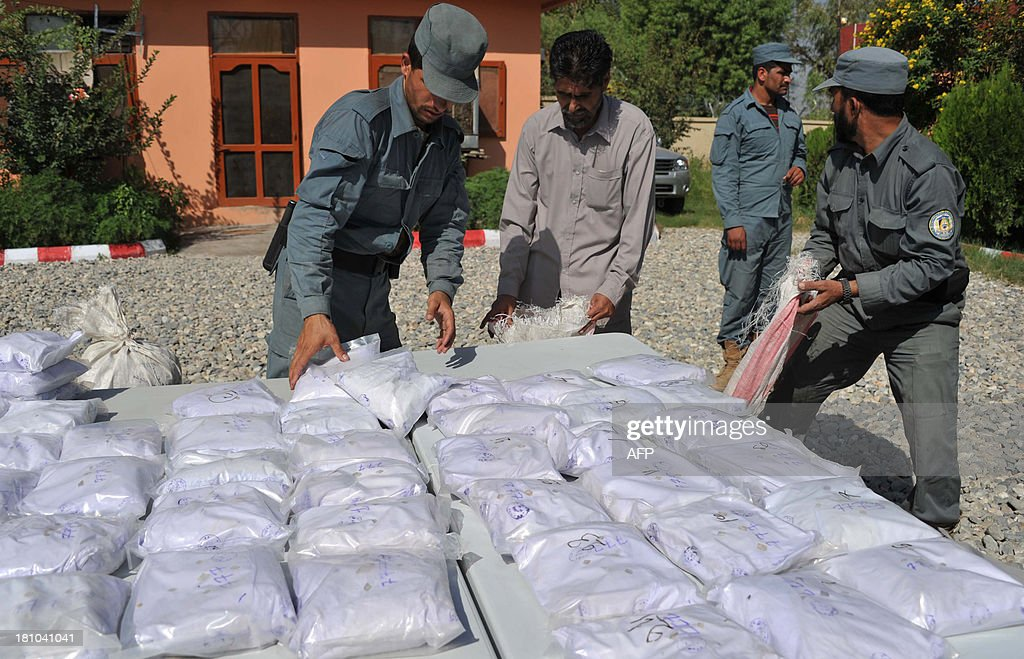 Afghan policemen count bags containing heroin as they are presented to the media at a police station in Jalalabad on September 19, 2013. Afghan police seized over 110 kilograms of heroin and arrested one man during an operation in the Sorkh Rud District of Nangarhar province, police officials said. AFP PHOTO / Noorullah Shirzada
