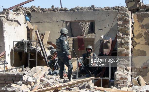 TOPSHOT Afghan policemen gather at the site of a suicide bombing attack on the police headquarters in Gardez capital of Paktia province on June 18...