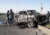 Afghan policemen inspect the site of a suicide car bomb in Lashkar Gah capital of Helmand province in southern Afghanistan on June17 2013 The police...