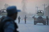 Afghan policemen keep watch as smoke billow in the background after an attack by Taliban militants on the Afghan intelligence service office in...