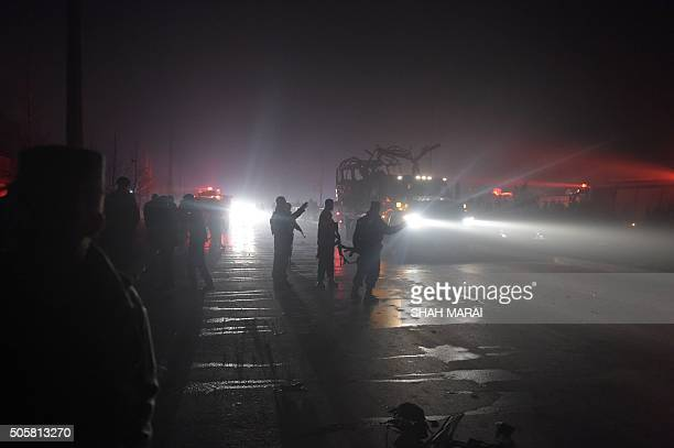 Afghan policemen keep watch as the wreckage of a bus which damaged by a suicide attack which killed seven is being transported on a truck in Kabul on...