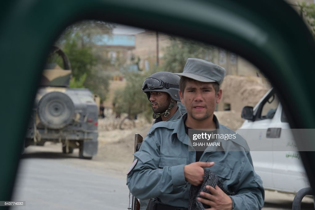 Afghan policemen keep watch at the site of a bomb attack on the outskirts of Kabul on June 30, 2016. At least 27 policemen were killed and 40 wounded after a bomb attack claimed by the Taliban struck a convoy of buses transporting police cadets in Kabul, the interior ministry said. / AFP / SHAH