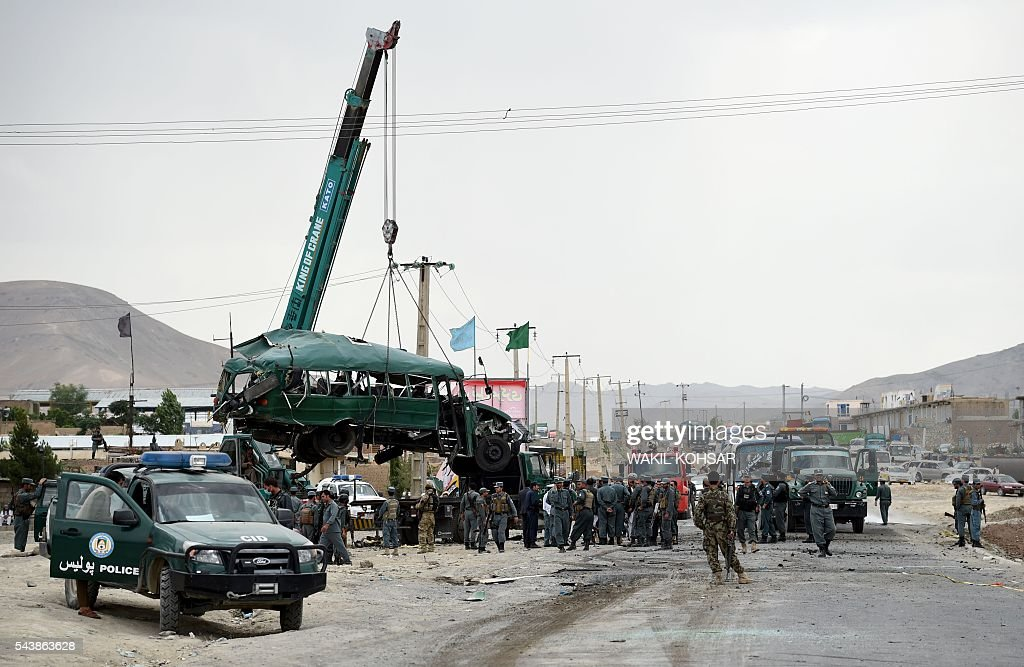 Afghan policemen look on as the wreckage of a bus is removed from the site of a suicide bomb attack that targeted a convoy of buses transporting police cadets on the outskirts of Kabul on June 30, 2016. A twin Taliban suicide attack has targeted a convoy of buses transporting Afghan police cadets in Kabul, killing 30 of them and wounding a further 58, Afghanistan's interior ministry said. / AFP / WAKIL