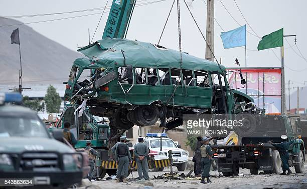 TOPSHOT Afghan policemen look on as the wreckage of a bus is removed from the site of a suicide bomb attack that targeted a convoy of buses...