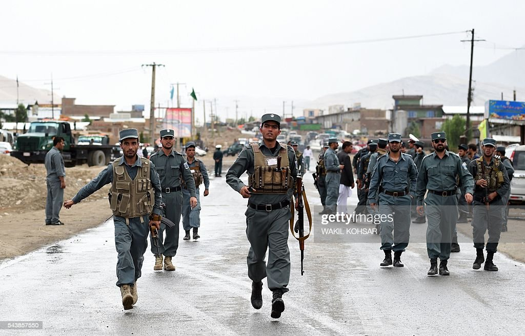 Afghan policemen run near the site of a suicide bomb near the site of a suicide bomb attack that targeted a convoy of buses transporting police cadets on the outskirts of Kabul on June 30, 2016. At least 27 policemen were killed and 40 wounded after a bomb attack claimed by the Taliban struck a convoy of buses transporting police cadets in Kabul, the interior ministry said. / AFP / WAKIL