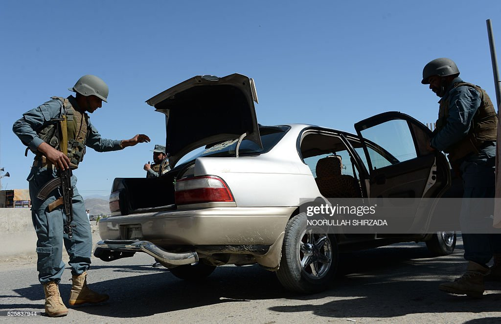 Afghan policemen search a vehicle in the city of Jalalabad, close to the border with Pakistan, on April 29, 2016, after reports that an aid worker from Perth has been kidnapped by armed men in Jalalabad. Australia was scrambling on April 29 to verify reports that an aid worker from Perth has been kidnapped by armed men in Afghanistan. The woman was taken in the city of Jalalabad, close to the border with Pakistan, on April 28, a government official in the area told AFP. / AFP / NOORULLAH