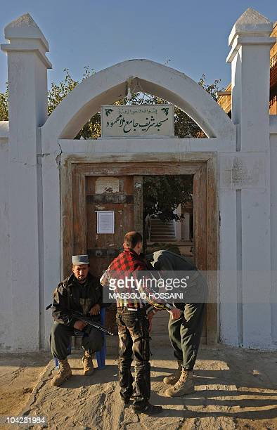 Afghan policemen search a voter as he arrives at the entrance to a polling station in Kabul on September 18 2010 Afghanistan began voting for a new...
