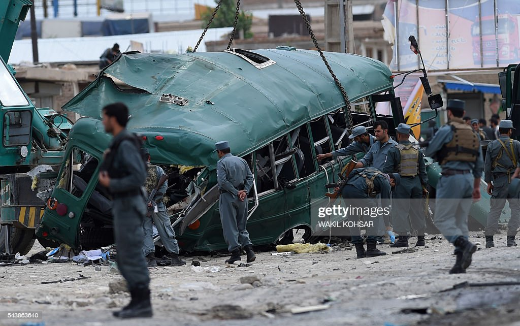 Afghan policemen search the wreckage of a bus at the site of a suicide bomb attack that targeted a convoy of buses transporting police cadets on the outskirts of Kabul on June 30, 2016. A twin Taliban suicide attack has targeted a convoy of buses transporting Afghan police cadets in Kabul, killing 30 of them and wounding a further 58, Afghanistan's interior ministry said. / AFP / WAKIL