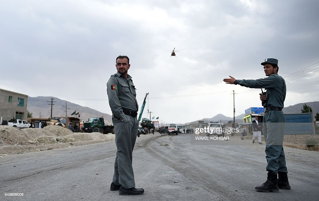 Afghan policemen stand guard as a helicopter flies over them near the site of a suicide bomb attack that targeted a convoy of buses transporting police cadets on the outskirts of Kabul on June 30, 2016. At least 27 policemen were killed and 40 wounded after a bomb attack claimed by the Taliban struck a convoy of buses transporting police cadets in Kabul, the interior ministry said. / AFP / WAKIL