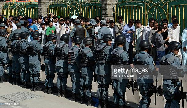 Afghan policemen stand guard as football fans wait in line before the start of the match between Afghanistan and Pakistan at the Afghanistan Football...