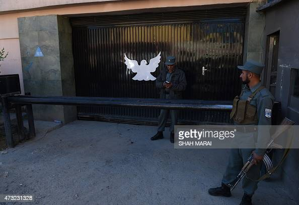 Afghan policemen stand guard at the entrance of the Park Palace guesthouse in Kabul on May 14 2015 An American was among five people killed when...