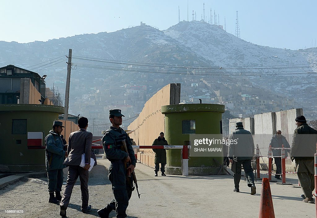 Afghan policemen stand guard at the entrance to police headquarters in Kabul on December 24, 2012. A female Afghan police officer has shot dead a foreign civilian adviser in Kabul police headquarters in an apparent 'green on blue' attack, the first of its kind by a woman, officials said. AFP PHOTO/ SHAH Marai