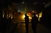 Afghan policemen stand guard at the site of a suicide attack at the foreign guesthouse in Kabul on November 27 2014 Gunfire and explosions erupted as...