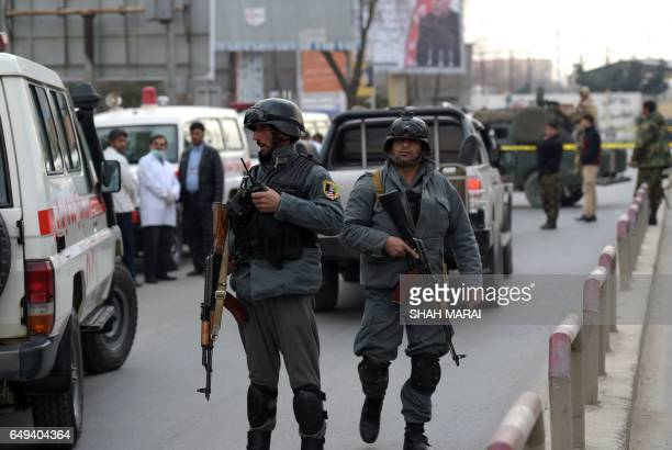 Afghan policemen stand guard near the site of an explosion in Kabul on March 8 2017 An explosion and gunfire rattled Kabul's diplomatic district as...