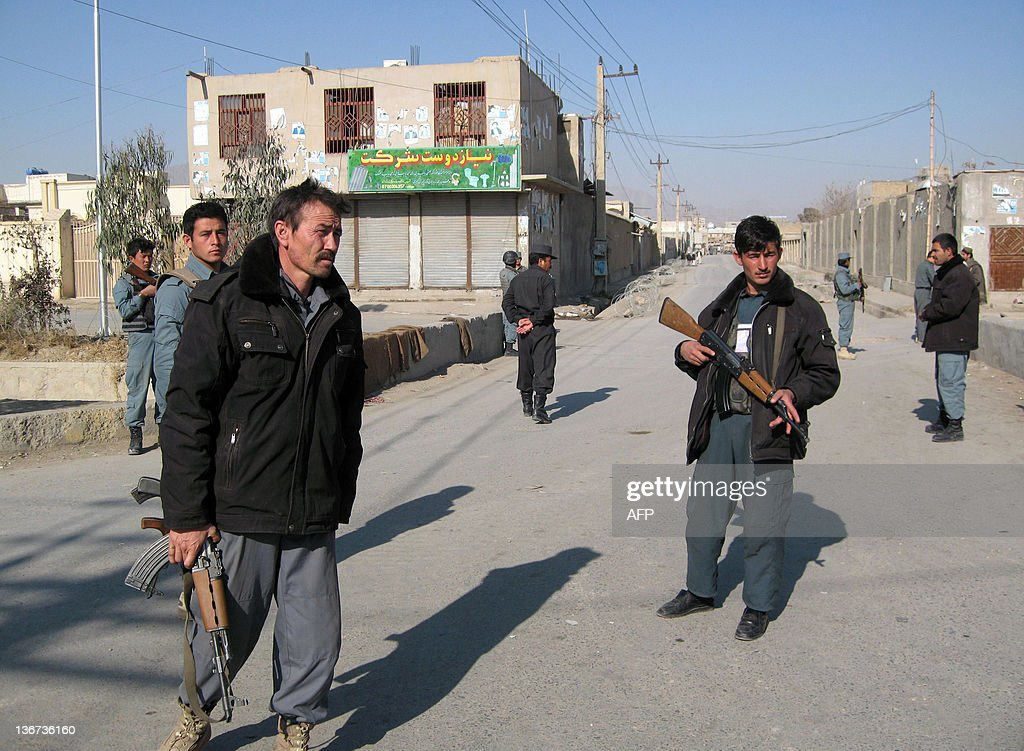 Afghan policemen stand guard outside the police headquarters after a a suicide attack in Kandahar on January 11 2012 The police chief of...