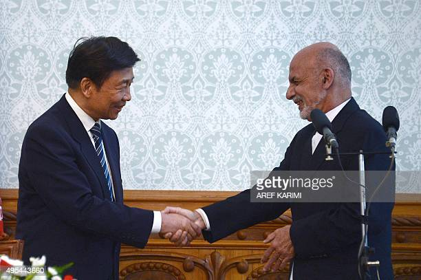 Afghan president Asharaf Ghani shakes hands with China's Vice President Li Yuanchao during a press conference at the Presidential Palace in Kabul on...