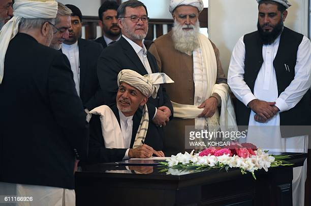 Afghan President Ashraf Ghani looks on as he signs a peace deal with Afghan warlord Gulbuddin Hekmatyar who was displayed on a video projector screen...