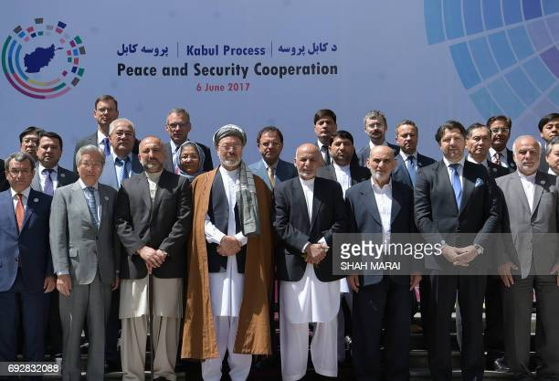 Afghan President Ashraf Ghani poses for a group photo with foreign delegates after an international peace conference at the Presidential Palace in...