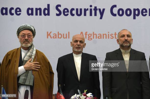 Afghan President Ashraf Ghani stands as the national anthem plays during an international peace conference at the Presidential Palace in Kabul on...