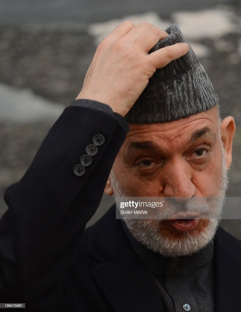 Afghan President Hamid Karzai adjusts his hat as he talks during a news conference at the Presidential Palace in Kabul on January 14, 2013. Afghan elders will decide on the key issue of whether US soldiers remaining in the country after 2014 will be granted immunity from prosecution, President Hamid Karzai said on 14 January. US President Barack Obama warned last week that no US troops would remain behind in Afghanistan after the withdrawal of NATO forces in 2014 unless they were granted immunity from prosecution in local courts. AFP PHOTO/ SHAH Marai
