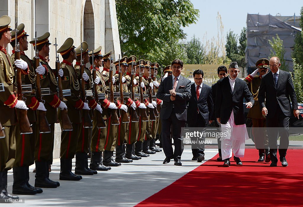 Afghan President Hamid Karzai (3R) and Italian Prime Minister Enrico Letta (R) walk prior to their meeting at the Presidential Palace in Kabul on August 25, 2013. Letta visited the base of the Italian contingent in Herat on his arrival in the country - Italy has around 3,000 soldiers in Afghanistan as part of NATO's International Security Assistance Force (ISAF). AFP PHOTO/POOL/SHAH Marai