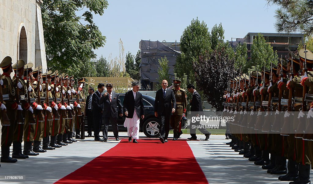Afghan President Hamid Karzai (CL) and Italian Prime Minister Enrico Letta (CR) walk prior to their meeting at the Presidential Palace in Kabul on August 25, 2013. Letta visited the base of the Italian contingent in Herat on his arrival in the country - Italy has around 3,000 soldiers in Afghanistan as part of NATO's International Security Assistance Force (ISAF). AFP PHOTO/POOL/SHAH Marai