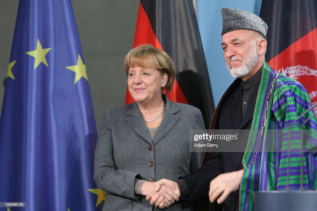 Afghan president Hamid Karzai shakes hands with German Chancellor Angela Merkel after a news conference in the German federal chancellery on December...