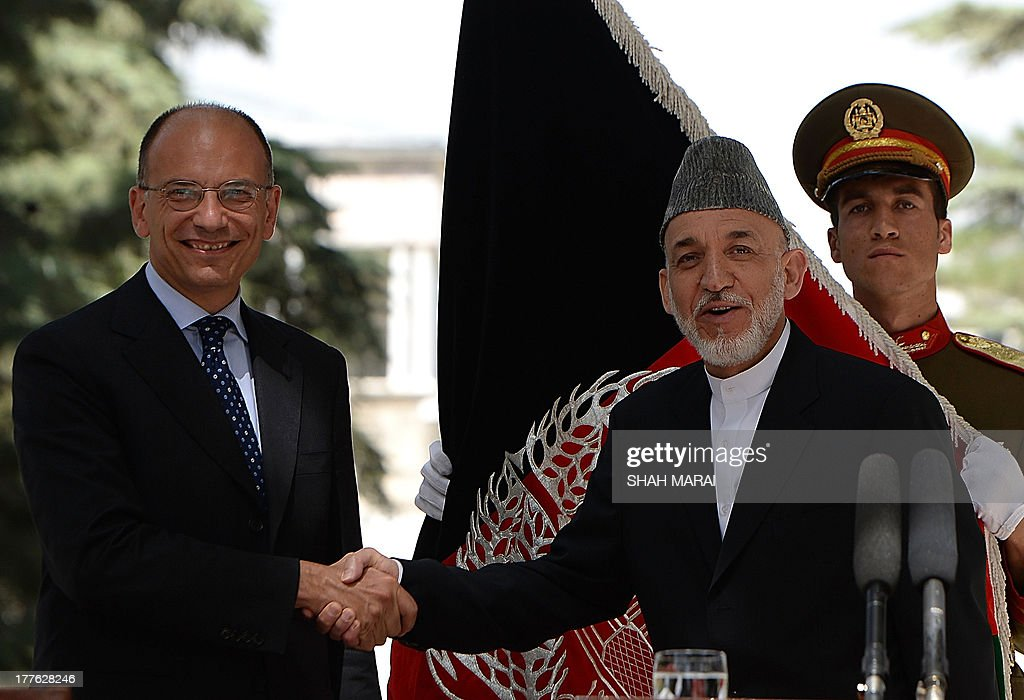 Afghan President Hamid Karzai shakes hands with Italian Prime Minister Enrico Letta (L) during a joint press conference at the Presidential palace in Kabul on August 25, 2013. Letta visited the base of the Italian contingent in Herat on his arrival in the country - Italy has around 3,000 soldiers in Afghanistan as part of NATO's International Security Assistance Force (ISAF). AFP PHOTO/ SHAH Marai