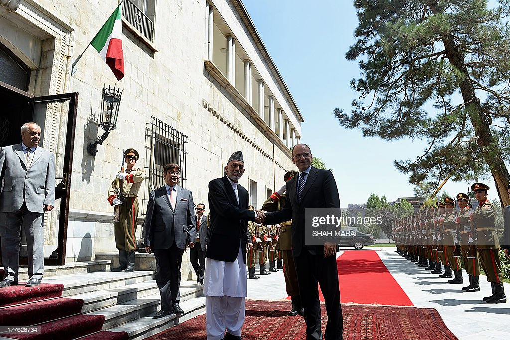 Afghan President Hamid Karzai (CL) shakes hands with Italian Prime Minister Enrico Letta (CR) prior to their meeting at the Presidential Palace in Kabul on August 25, 2013. Letta visited the base of the Italian contingent in Herat on his arrival in the country - Italy has around 3,000 soldiers in Afghanistan as part of NATO's International Security Assistance Force (ISAF). AFP PHOTO/POOL/SHAH Marai