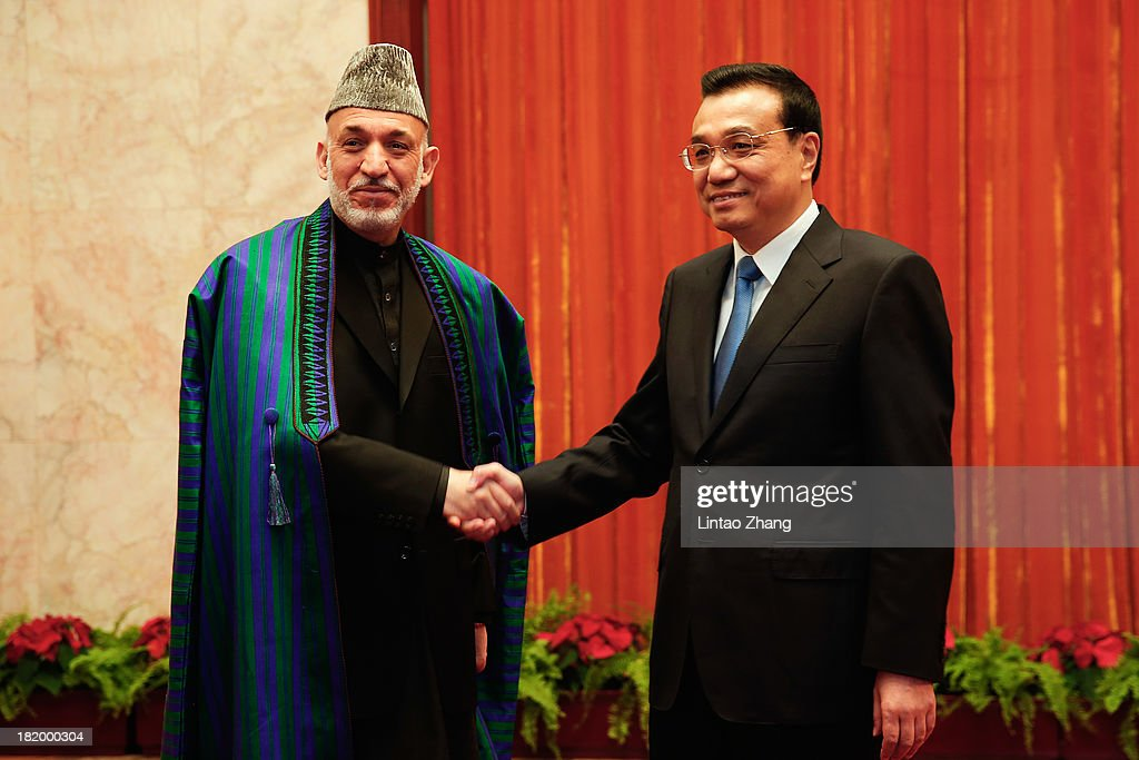 Afghan President Hamid Karzai shankes hands with Chinese Premier Li Keqiang at the Great Hall of the People on September 23 2013 in Beijing China...