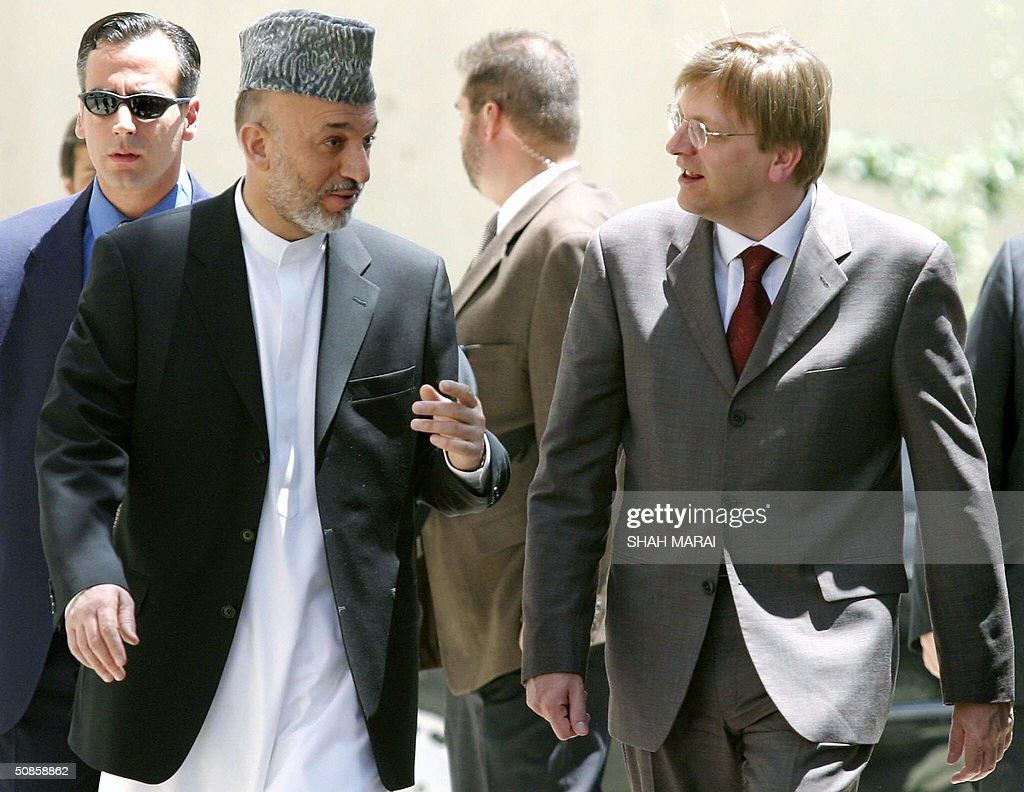 Afghan President Hamid Karzai (L) talks with Belgian Prime Minister Guy Verhofstadt (R) as they walk towards a press conference in the grounds of the Presidential Palace in Kabul, 20 May 2004. Verhofstadt is in Kabul for one day to visit Karzai and to meet with officials from the NATO-led International Security Assistance Force (ISAF) of peacekeeping troops to which Belgium contributes some 290 troops. Belgium's ISAF contingent are mostly are deployed providing security at Kabul International Airport. Command of ISAF will be taken over from Canada by Eurocorps in August with Belgium expected to be among the major contributors to the force. AFP PHOTO/ Shah Marai
