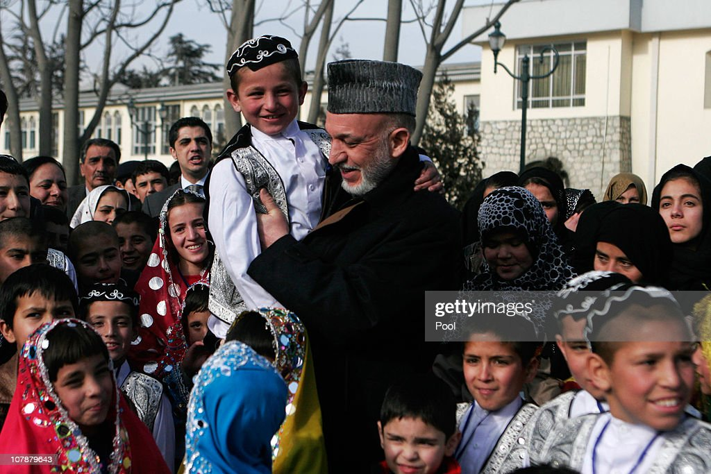 Afghan President Hamid Karzi center holds an afghan orphan boy as other orphans looks on during a vist to Presidential Palace on January 5 2010 in...