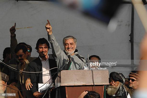 Afghan presidential candidate Abdullah Abdullah gestures to the crowd as he holds a rally for thousands of supporters in his home province on March...