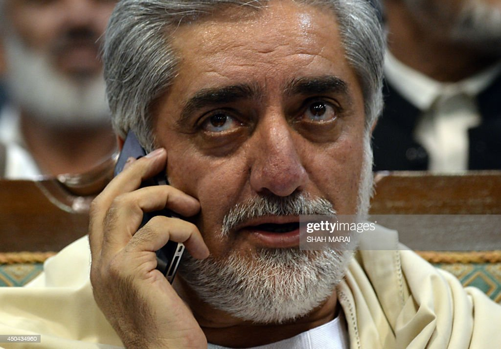 Afghan presidential candidate Abdullah Abdullah speaks on his mobile phone during a gathering on the last day of campaigning in Kabul on June 11, 2014. Afghanistan's election will go to a run-off vote between former foreign minister Abdullah Abdullah and ex-World Bank economist Ashraf Ghani, results confirmed, as the country enters a new era without NATO combat troops. The head-to-head election, scheduled for June 14, will choose a successor to President Hamid Karzai in Afghanistan's first democratic transfer of power. AFP PHOTO/SHAH Marai