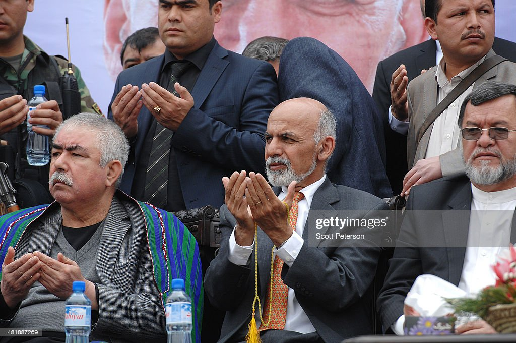 Afghan Presidential Candidate Ashraf Ghani Ahmadzai (center) and his vice presidential running mate Gen. Rashid Dostum (left) hold up their hands during a rally for thousands of supporters at the Ghazi stadium on April 1, 2014 in Kabul, Afghanistan. Mr. Ghani is a frontrunner in the April 5 vote to succeed President Hamid Karzai, in an election that is seen as a test of stability that will ensure continued Western donor aid for a nation torn by a Taliban insurgency. The Ghazi stadium is known as the site of amputations and executions during Taliban rule in the late 1990s.