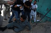 Afghan protesters beat a policeman after a suicide attack that targeted crowds of minority Shiite Hazaras during a demonstration at the Deh Mazang...