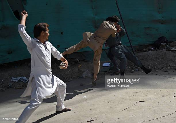 TOPSHOT Afghan protesters beat a policeman after a suicide attack that targeted crowds of minority Shiite Hazaras during a demonstration at the Deh...