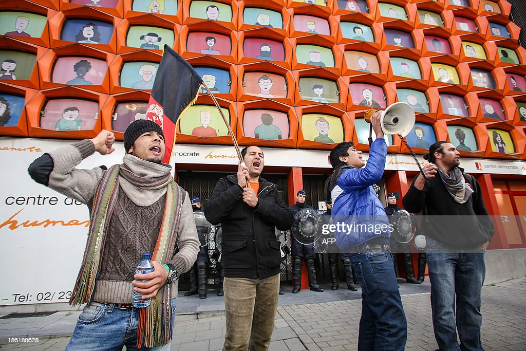 Afghan protesters shout slogans in front of the Belgian Christian democratic party cdH headquarters, while police guard the entrance, during a demonstration of Afghan refugees on the Wetstraat - rue de la Loi in Brussels on October 29, 2013.