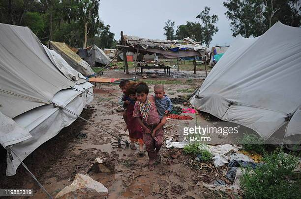 Afghan refugee children residing in Pakistan who survived last year's flooding walk at a camp in Nowshera on July 26 2011 Pakistan has failed to...