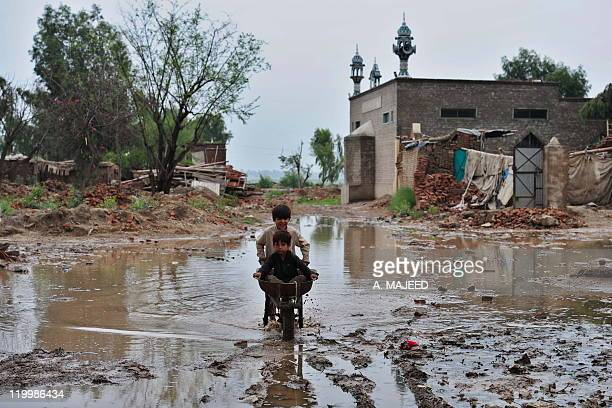 Afghan refugee children residing in Pakistan who survived last year's flooding play following rain at a camp in Nowshera on July 26 2011 Pakistan has...