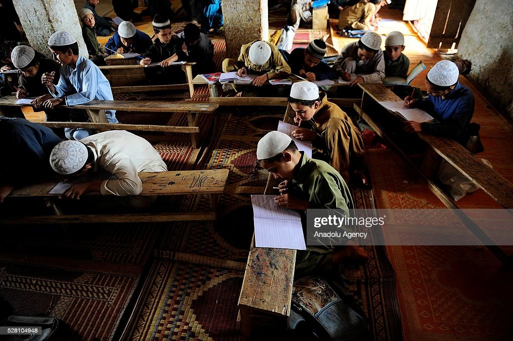 Afghan refugee kids try to study on the floor in a refugee village outside Islamabad, Pakistan on May 4, 2016.